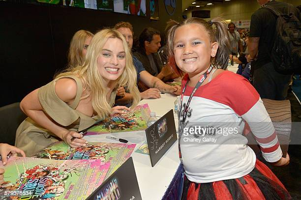 Actress Margot Robbie from the cast of Suicide Squad film poses with a cosplayer in DC's 2016 Comic-Con booth at San Diego Convention Center on July...