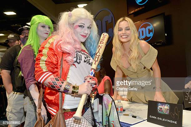 Actress Margot Robbie from the cast of Suicide Squad film poses with a cosplayer in DC's 2016 ComicCon booth at San Diego Convention Center on July...