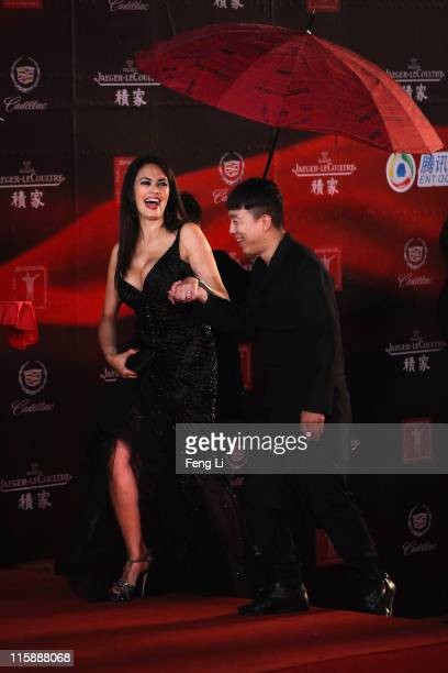 Actress Maria Grazia Cucinotta and actor Huang Bo arrive at the opening ceremony of the 14th Shanghai International Film Festival on June 11 2011 in...