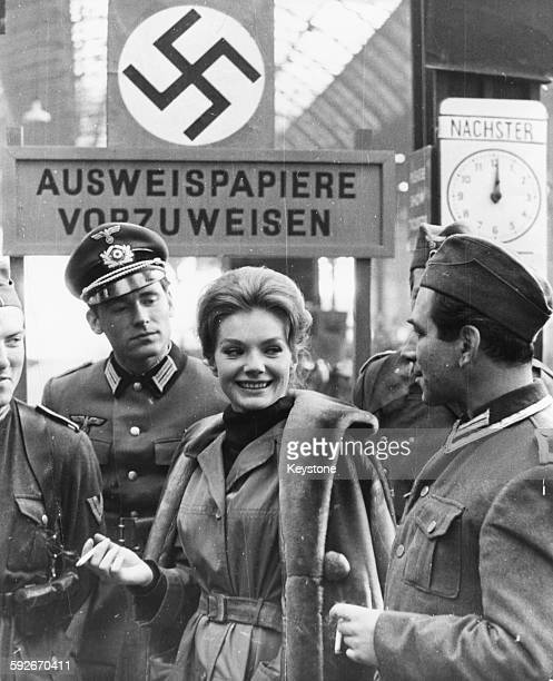 Actress Maria Perschy talking to a group of actors in Nazi uniform filming scenes for the film 'Passport to Courage' at London Bridge Station England...