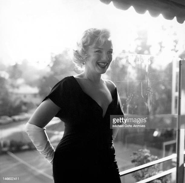 Actress Marilyn Monroe attends a party held in her honor wearing a black dress and white gloves at the Beverly Hills Hotel on July 8, 1958 in Beverly...