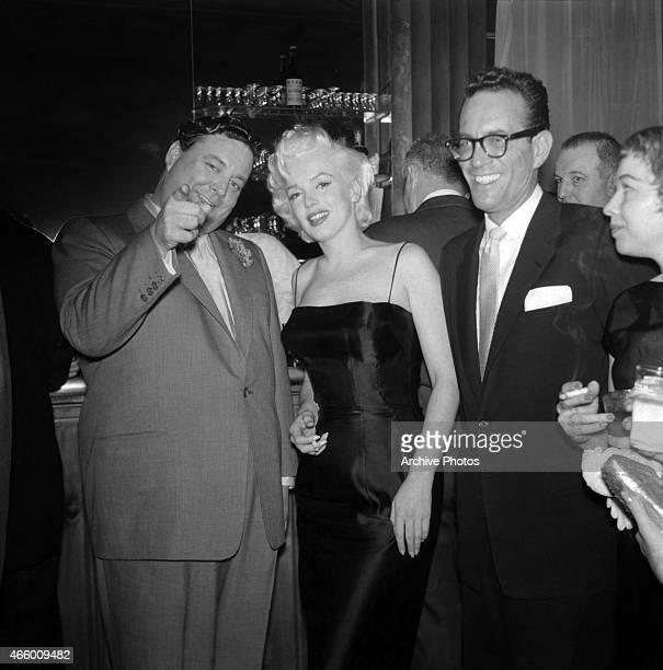 Actress Marilyn Monroe chats with Jackie Gleason at is birthday party at Toots Shor's Restaurant on February 26 1955 in New York City New York