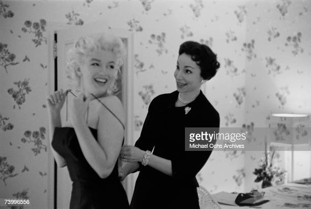 Actress Marilyn Monroe gets help dressing from Judy Goetz in her hotel room on March 24 1955 at the Ambassador Hotel in New York City New York