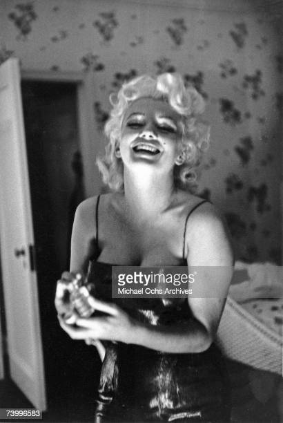 Actress Marilyn Monroe gets ready to go see the play Cat On A Hot Tin Roof playfully applying her make up and Chanel No 5 Perfume on March 24 1955 at...