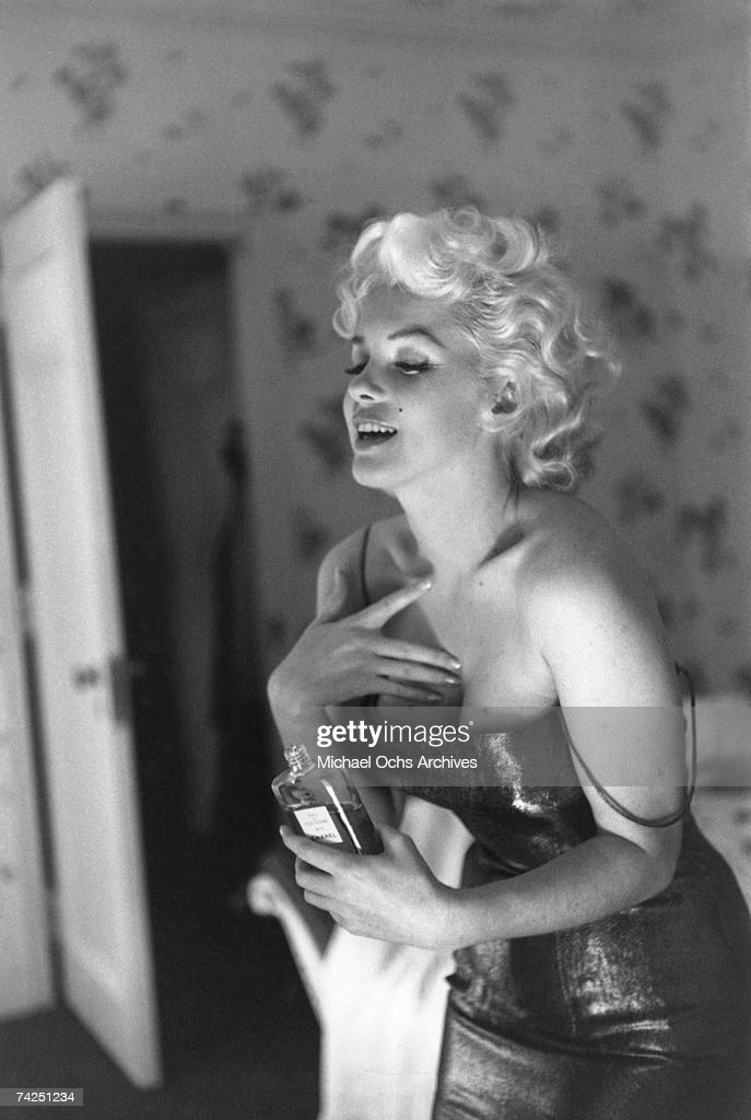 Actress Marilyn Monroe gets ready to go see the play 'Cat On A Hot Tin Roof' playfully applying her make up and Chanel No. 5 Perfume on March 24, 1955 at the Ambassador Hotel in New York City, New York.