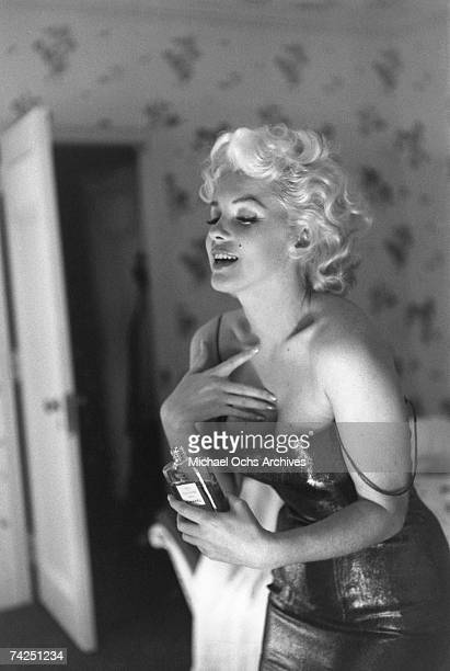 "Actress Marilyn Monroe gets ready to go see the play ""Cat On A Hot Tin Roof"" playfully applying her make up and Chanel No. 5 Perfume on March 24,..."