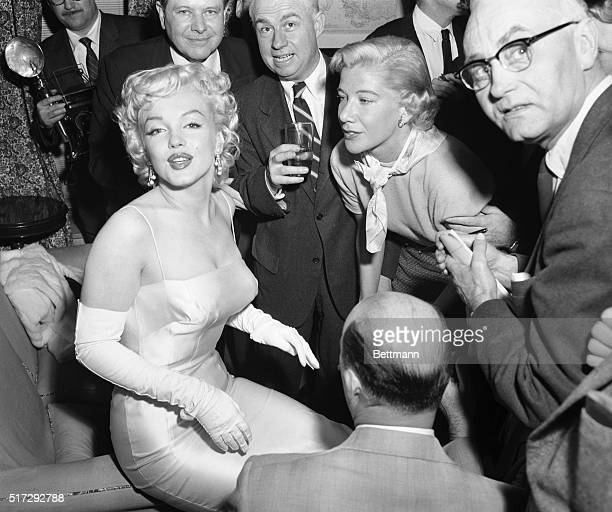 Actress Marilyn Monroe is surrounded by photographers and journalists as she is interviewed by Phyllis Battelle , who writes in the International...