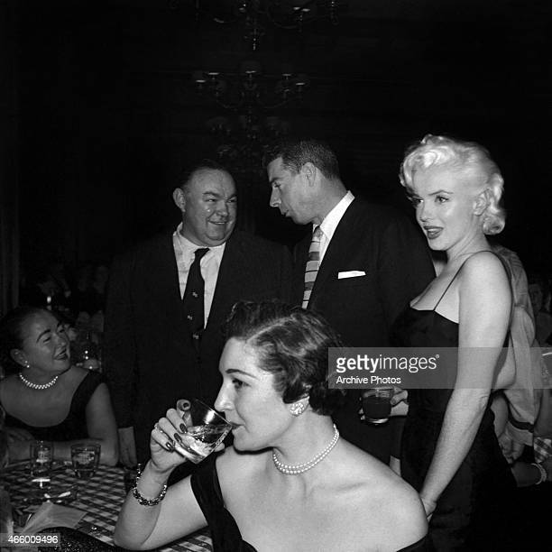 Actress Marilyn Monroe looks on as former husband Joe DiMaggio chats with a guest at Jackie Gleason's birthday party at Toots Shor's Restaurant on...