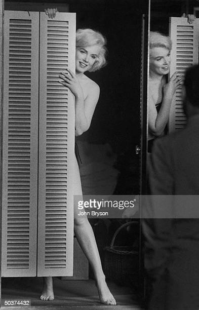 Actress Marilyn Monroe peering out at her husband Arthur Miller fr behind door after putting on sexy bikini bathing suit she purchased w the price...