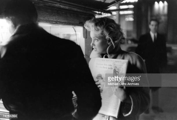 Actress Marilyn Monroe picks up a copy of the New York Dail Post newspaper at a newstand in March 1955 in New York City New York