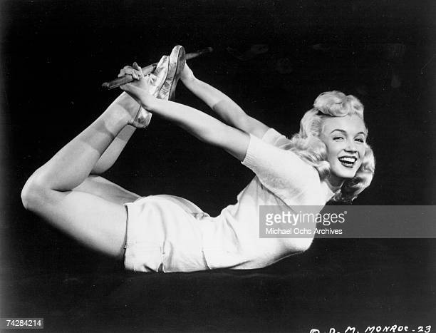 Actress Marilyn Monroe poses for a film publicity shot holding her legs behind her back with a stick while laying on her stomach in circa 1950