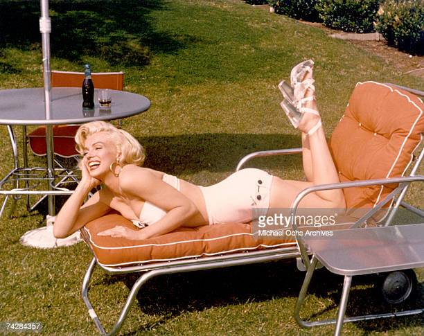 Actress Marilyn Monroe poses for a portrait in a bathing suit and high heels with a bottle of CocaCola in a glass on a table behind her in circa 1953