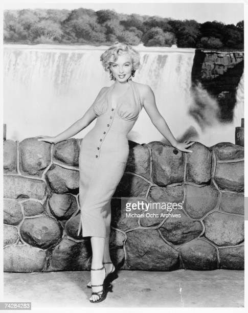 Actress Marilyn Monroe poses for a portrait in front of Niagara Falls dressed as Rose Loomis from the film Niagara which was released on January 21...