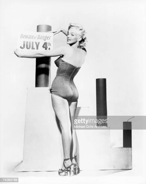 Actress Marilyn Monroe poses for a portrait wearing a bikini with some oversized fireworks and a sign that reads Beware of Danger July 4th in circa...