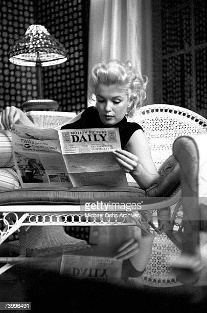 Actress Marilyn Monroe reads the newspaper 'Motion Picture Daily' as she relaxes on a couch in her hotel room at the Ambassador Hotel on March 24...