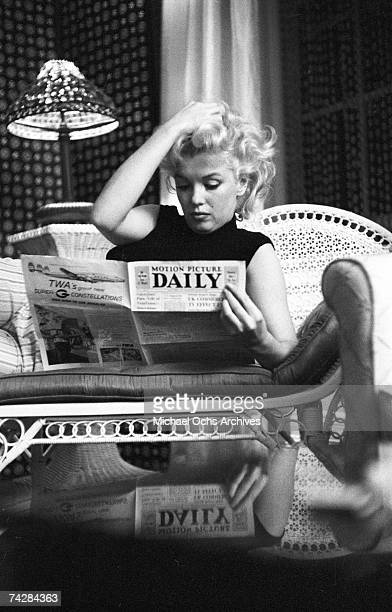 Actress Marilyn Monroe reads the newspaper Motion Picture Daily as she relaxes on a couch in her hotel room at the Ambassador Hotel on March 24 1955...