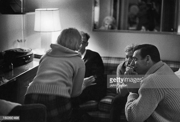 Actress Marilyn Monroe speaking to husband Arthur Miller while Simone Signoret and Yves Montand listen During the filming of 'Lets Make Love' 1960