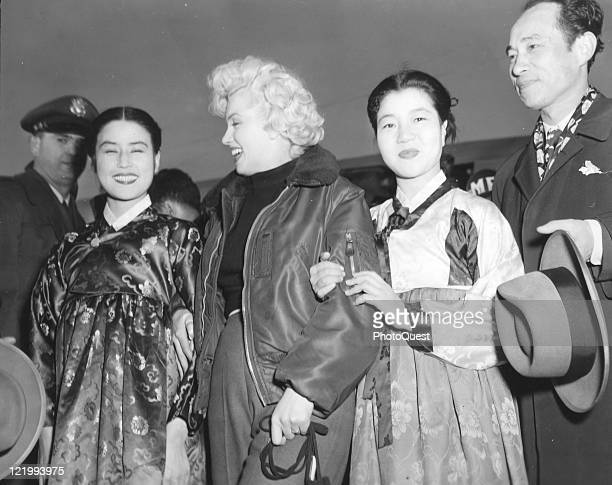 Actress Marilyn Monroe stands with three prominent Korean thespians upon her arrival at K2 Airfield in Korea to entertain the troops