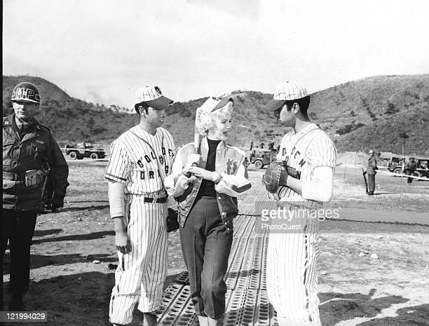 Actress Marilyn Monroe talks with Miran and April twin brothers from the Puerto Rican baseball team of the 25th Infantry Division during her visit to...