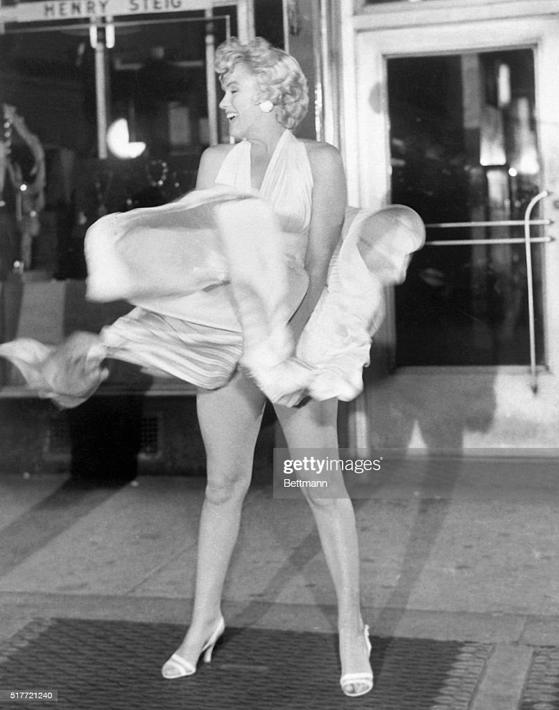 Actress Marilyn Monroe tries to hold down her dress as wind from a subway grate blows it upward during filming of The Seven Year Itch motion picture in Manhattan.