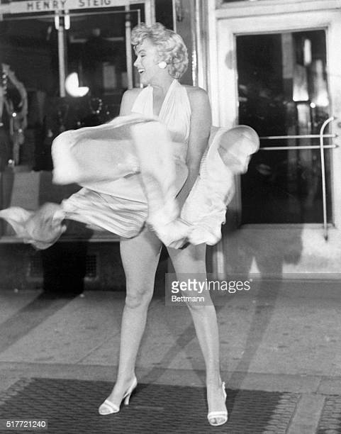 Actress Marilyn Monroe tries to hold down her dress as wind from a subway grate blows it upward during filming of The Seven Year Itch motion picture...
