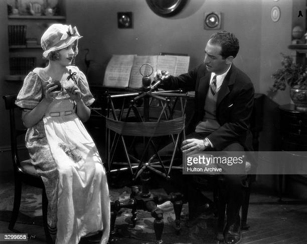 Actress Marion Davies and director Sidney Franklin test out a device for winding wool on the set of their latest film the MGM romance 'Quality Street'