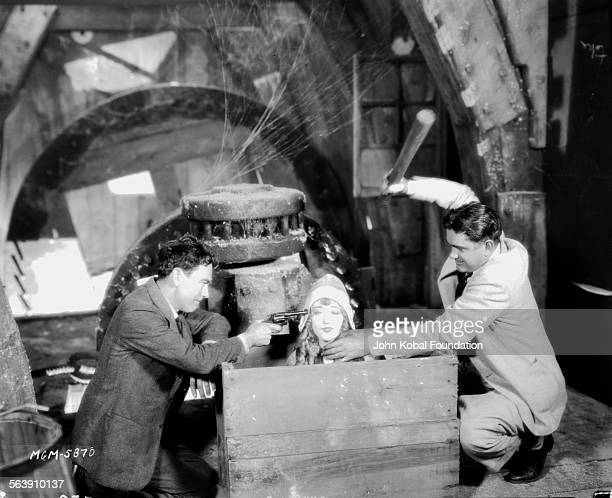 Actress Marion Davies is sitting in a box with two actors holding a gun and a bat to her head in a scene fro the film 'The Red Mill' for MGM Studios...