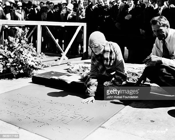 Actress Marion Davies making her handprints in cement, along with her signature, outside Grauman's Chinese Theatre in Hollywood, for MGM Studios, May...