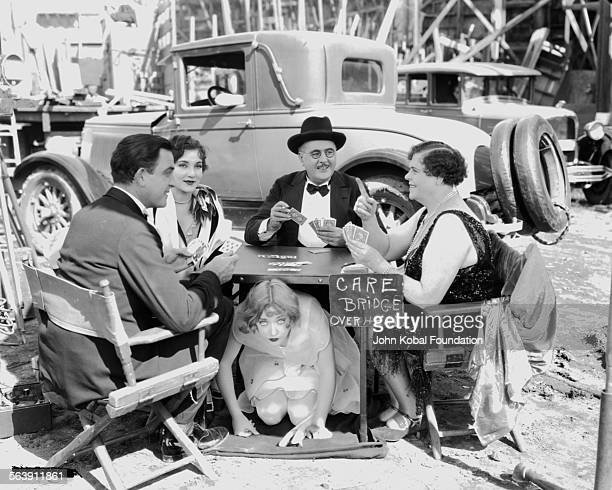 Actress Marion Davies playing a game of a cards with a group of actors at an outdoor table during the filming of a movie for MGM Studios November 3rd...