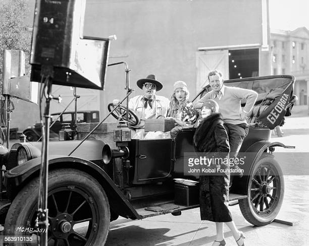 Actress Marion Davies sitting in a car with a group of other actors on a film set for MGM Studios April 10th 1928