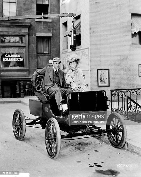 Actress Marion Davies sitting in a car with an actor on a film set for MGM Studios February 16th 1930