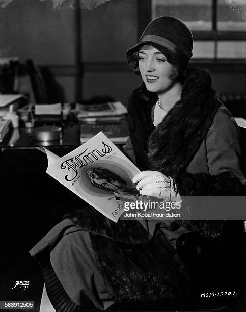 Actress Marion Davies wearing her coat and hat as she reads a film magazine for MGM Studios 1927