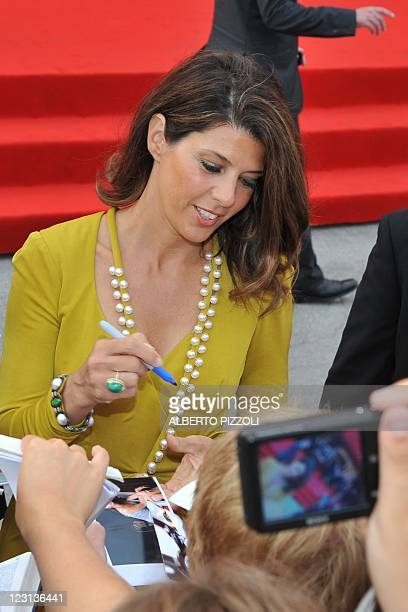 """Actress Marisa Tomei signs autographs as she arrives for the opening ceremony and the screening of """"The Ides of March"""" during the 68th Venice..."""