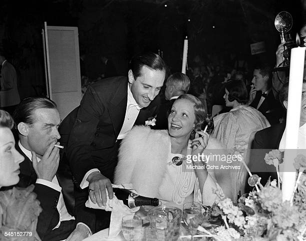 Actress Marlene Dietrich smiles at actor Basil Rathbone as he pours her a drink during an event in Los Angeles California