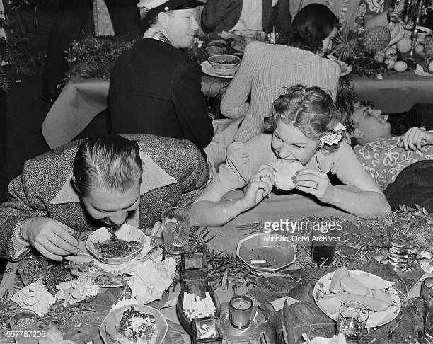 Actress Martha Raye bites some bread during a dinner party in Los Angeles California
