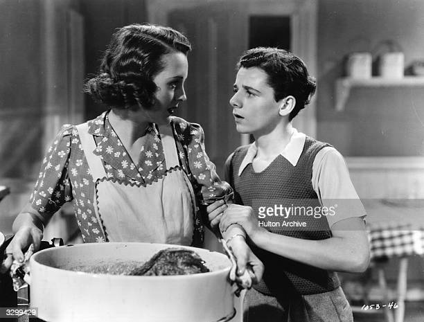 Actress Mary Astor talks with Freddie Bartholomew over a large cooking pot in a scene from the film 'Listen Darling' in which three children try to...