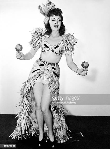 Actress Mary Brodel dons her newspaper headlines and performs a War Extra dance with maracas Hollywood California early 1940s