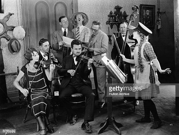 Actress Mary Pickford formerly Gladys Smith directs her orchestra and singing trio in a rendering of 'Little Annie Rooney' From left to right the...