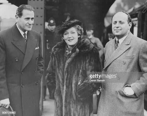 Actress Mary Pickford with film producers David Rose of Metro Goldwyn Meyer and Murray Silverstone of United Artists as she arrives at Waterloo...