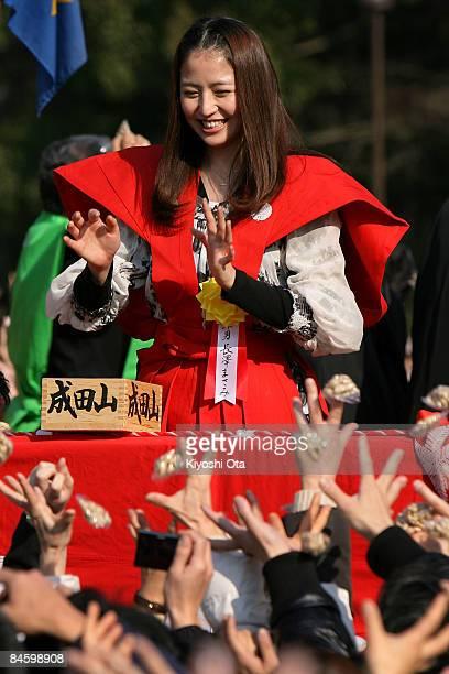Actress Masami Nagasawa throws packs of beans to visitors during a beanscattering ceremony at Shinshoji Temple on February 3 2009 in Narita Chiba...