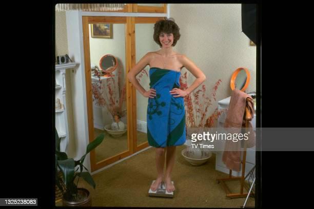 Actress Maureen Lipman weighing herself in a towel, circa 1982.