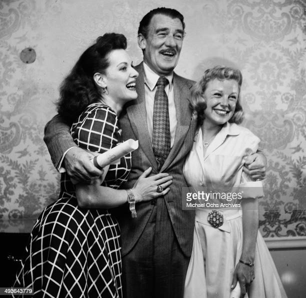 Actress Maureen O'Hara actor Walter Pidgeon and actress June Allyson pose at a party in Los Angeles California