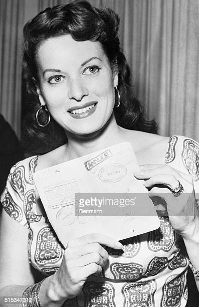 Actress Maureen O'Hara displays her passport to newsmen to support her contention that she was not even in the United Sates at the time she is...