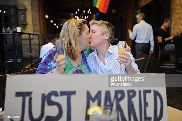 Actress Megan Cavanagh and her wife filmaker Anne Chamberlain kiss at the Abbey bar in West Hollywood California on June 26 2013 The pair who were...