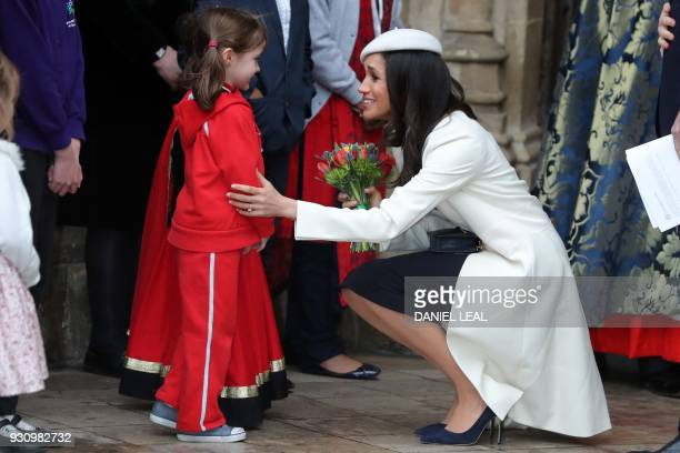 TOPSHOT US actress Meghan Markle fiancee of Britain's Prince Harry receives a posy of flowers from a young girl after attending a Commonwealth Day...