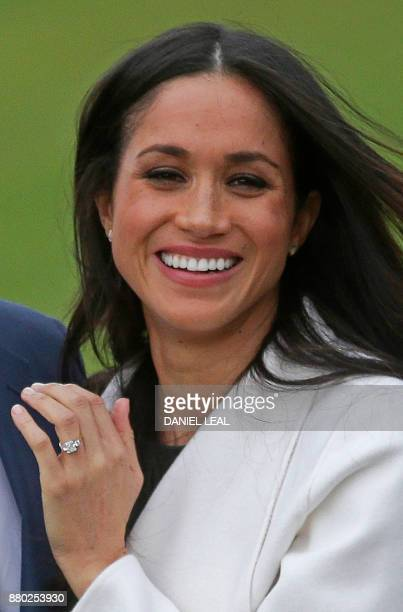 US actress Meghan Markle shows off her engagement ring as she poses with her fiancée Britain's Prince Harry in the Sunken Garden at Kensington Palace...