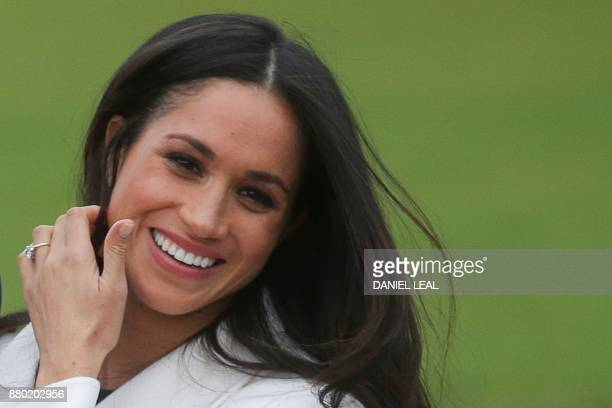 US actress Meghan Markle shows off her engagement ring she poses with her fiancée Britain's Prince Harry in the Sunken Garden at Kensington Palace in...