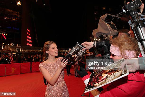 Actress Melanie Laurent signs autographs while arriving for the 'Aloft' premiere during 64th Berlinale International Film Festival at Berlinale...