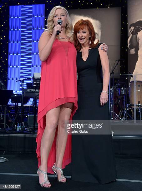 Actress Melissa Peterman and emcee Reba McEntire speak onstage during Muhammad Ali's Celebrity Fight Night XX held at the JW Marriott Desert Ridge...