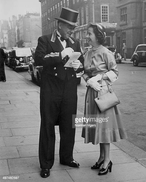 Actress Merle Oberon getting a tip from Commissionaire Warburton of Claridge's Hotel as she leaves for Royal Ascot London June 13th 1950
